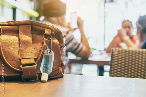 Fototapeta Mini portable alcohol gel bottle to kill Corona Virus(Covid-19) hang on a brown leather shoulder bag on table in coffee shop