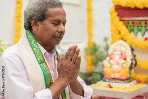 Elder man offering Bhajan or hymn in front of Lord Ganesha Idol during Ganesha or vinayaka Chaturthi festvial ceremony at home Wallpaper Mural