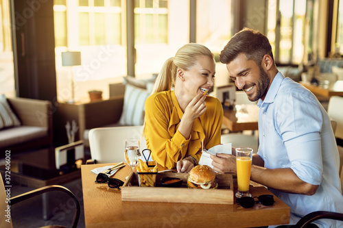 Foto Cheerful couple having fun during lunch time in a restaurant.
