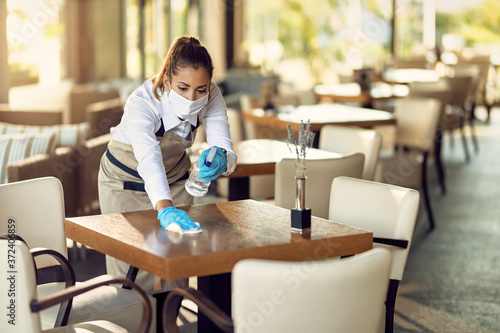 Fototapeta Waitress with a face mask and gloves cleaning tables with disinfectant in a cafe. obraz