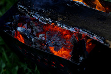 Burning Log Of Wood Close-up Taken. Smoldering Fire. Fire Flames On The Green Garden Background. Firewood Burning On Grill. Time For Bbq And Relaxing Concept.