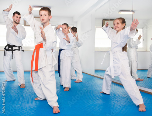 Obraz na plátně Children trying new martial moves in the practice during a karate class in a gym