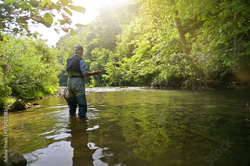 Fotografiet fly fisherman in summer fishing in a mountain river with waders and a cap