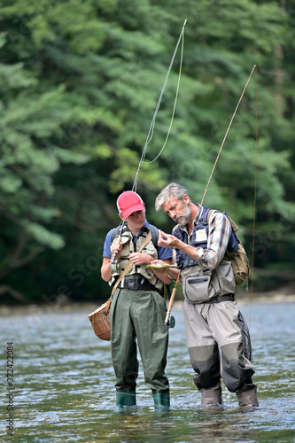 Obraz na plátne A father and his son fly fishing in summer on a beautiful trout river with clear