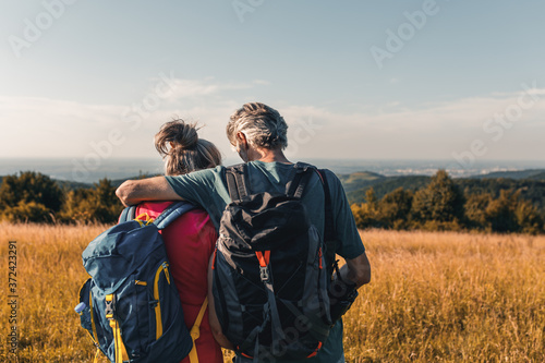 Fotografia Active senior couple hiking in nature with backpacks, enjoying their adventure at sunset