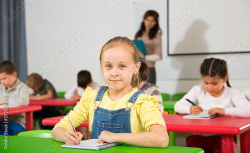 Fotografía Portrait of little assiduous girl with pen and notebook at lesson in elementary school