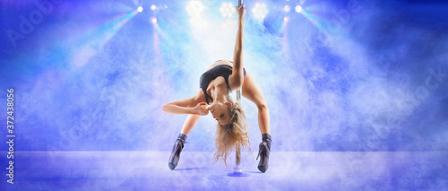 attractive pole dance woman in the smoke and rays of light