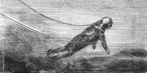 Fotografiet Vintage diver in suit in the old book Encyclopedia by I