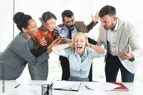 Photo Colleagues screaming at businesswoman in office