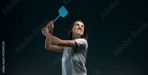 Angry woman killing mosquitoes with a fly swatter Canvas Print