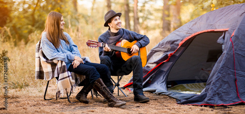 Portrait of young couple sitting on camp chair with guitar near camp tent Wallpaper Mural