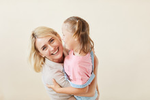 Portrait Of Happy Mother Embracing Her Daughter With Down Syndrome And Smiling At Camera Isolated On White Background