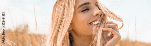 Papel de parede horizontal image of excited blonde woman touching hair while looking away