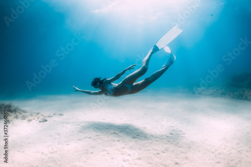 Fotografering Attractive woman freediver glides and posing over sandy bottom with fins