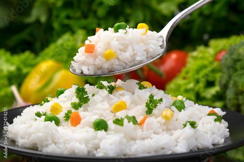 Fototapeta Cooked rice porridge, served with herbs and vegetables on black plate obraz