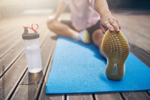 Obraz na plátně Female spending time outside on yoga mat