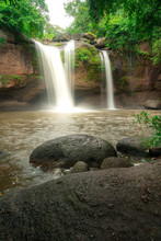 A Terrific Waterfall With Severe Water Stream Down From High Cliff, Surrounded By Greenery Rainforest Jungle Environment. Photo Taken With Long Exposure For Smoothed Water Line.