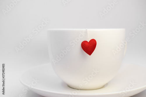 on the saucer is a white Cup on which hangs a red heart on a string Fotobehang