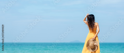 Fototapeta Summer vacations. Lifestyle woman relax and chill on beach background.  Asia happy young people wearing yellow dress fashion summer trips walking enjoy  tropical beach.  obraz