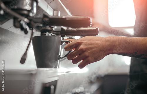 Fototapeta Barista making coffee in coffee machine