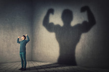 Confident Man Flexing Muscles Imagine Super Power As Casting A Shadow Of Muscular Bodybuilder Showing Biceps. Strong Person Facing His Fears. Personal Development, Inner Strength, Motivation Concept.