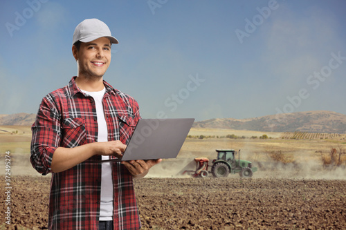 Fototapeta Agricultural engineer in a field with a laptop computer and a tractor plowing the soil obraz