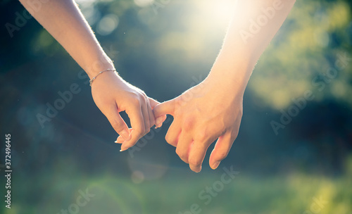 Foto young couple holding hands at sunset, close-up detail of pinkies in sunlight, lo