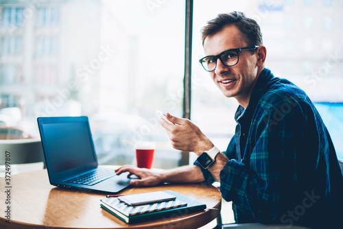 Fotografia, Obraz Half length portrait of handsome cheerful male developer in cool spectacles using modern technology during remote work in cafe