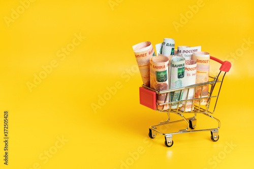 Leinwand Poster Russian ruble banknotes in shopping cart on yellow background