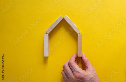 Male hand builds a model of a wooden house from wooden blocks Canvas-taulu