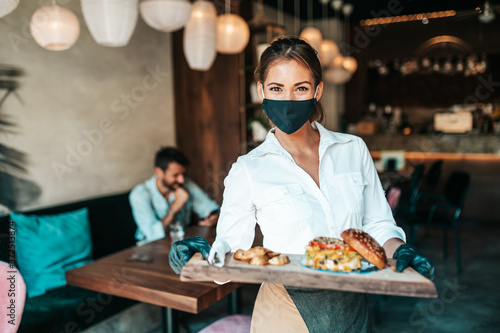 Fototapeta Beautiful young waitress with face protective mask serving delicious burger to middle age male customer