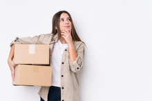 Young Caucasian Woman Moving To A New Home Looking Sideways With Doubtful And Skeptical Expression.