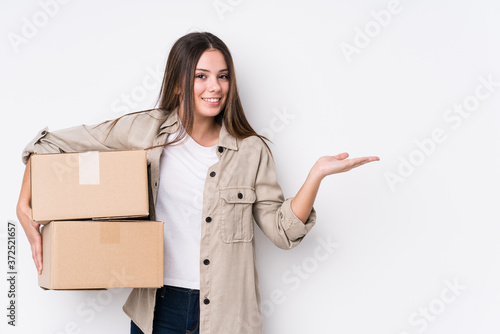 Tela Young caucasian woman moving to a new home showing a copy space on a palm and holding another hand on waist