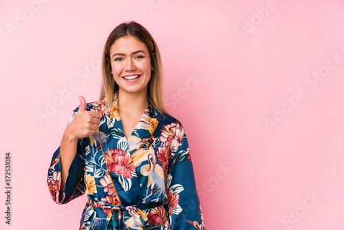 Fotografia Young caucasian woman wearing pajamas smiling and raising thumb up