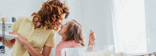 Fotografie, Obraz selective focus of mother standing face to face with daughter kneading dough in