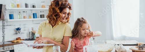 horizontal concept of mother holding cookbook while daughter preparing dough in Fototapet