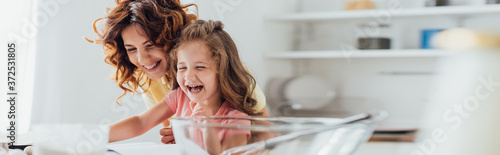 Fotomural selective focus of excited mother and daughter laughing while cooking in kitchen