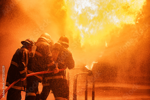Fotografia, Obraz Firefighter using extinguisher or Twirl water fog type fire extinguisher to spray water from hose for fire fighting with fire flame on fuel and control fire for safety in plant of industrial area