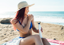 Beautiful Caucasian Girl Sitting In A Hat, Red Hair, White Dress, And Blue Bikini, Sunbathing On A Beach With A Blue Sky
