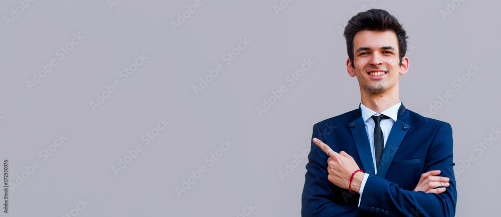 Fototapeta Young handsome businessman with beaming smile pointing with finger