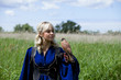 beautiful girl in a long blue medieval dress with a hunting Falcon on her glove