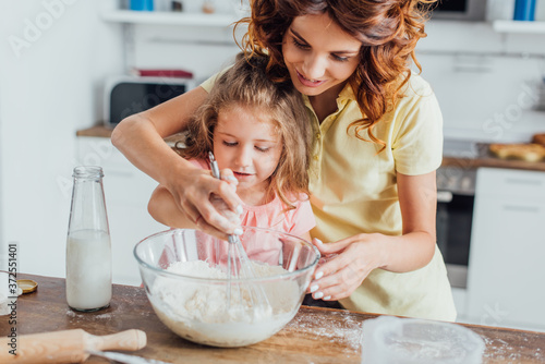 Fototapeta selective focus of mom kneading dough in glass bow near daughter and bottle of m