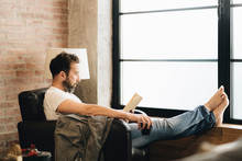 Mature Man Sitting Barefoot In Armchair, Reading Bok