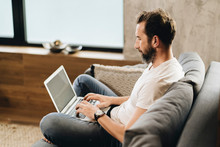 Mature Man Sitting On Couch, Using Laptop
