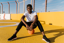 Young Man Sitting On Basketball In Court During Sunny Day