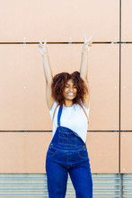 Cheerful Young Woman With Arms Raised Standing Against Wall In City