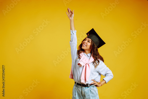 Fotografia Graduate woman in a graduation hat on her head posing on a yellow background