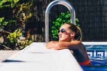 Woman Enjoying Sunlight At Pool Edge