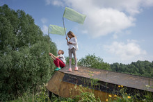Friends Catching Butterflies With Nets On Abandoned Boat Against Sky