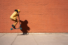 Boy Performing Stunt With Push Scooter On Sidewalk Against Brick Wall During Sunny Day